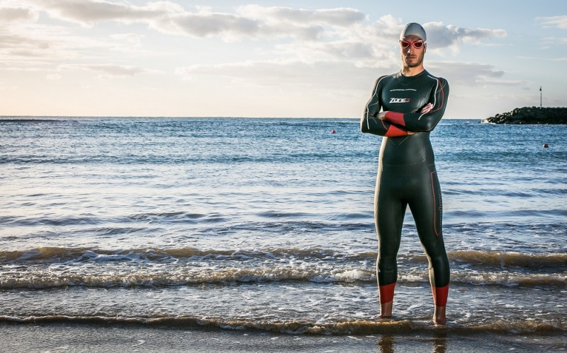 A man posing by the sea in a Zone3 wetsuit